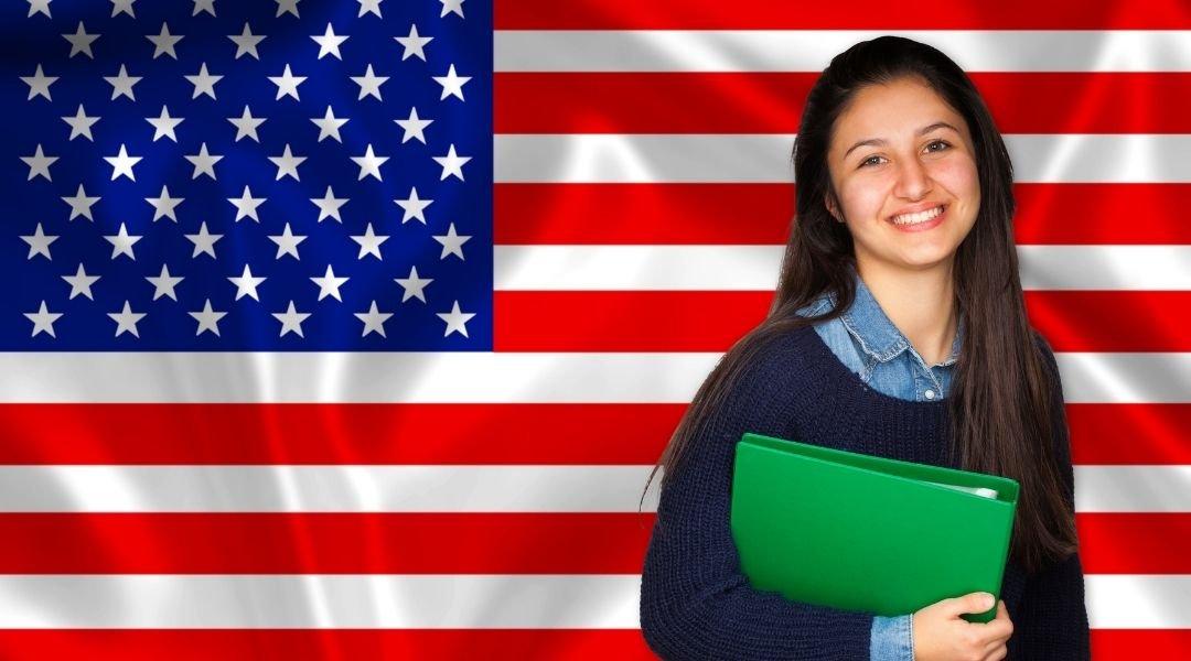 estudante em frente de uma bandeira dos estados unidos. Saiba aqui sobre o valor do visto americano