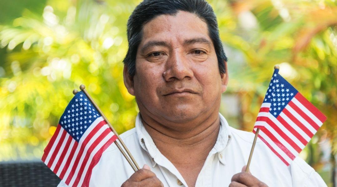 imigrante segurando duas bandeirinhas dos estados unidos