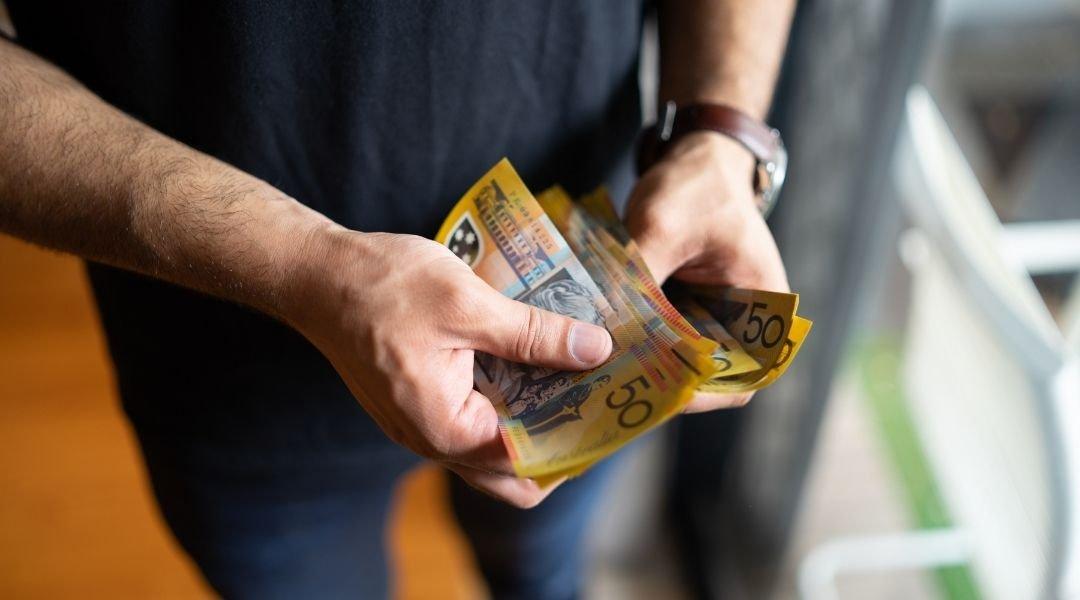 um homem tirando dinheiro australiano da carteira