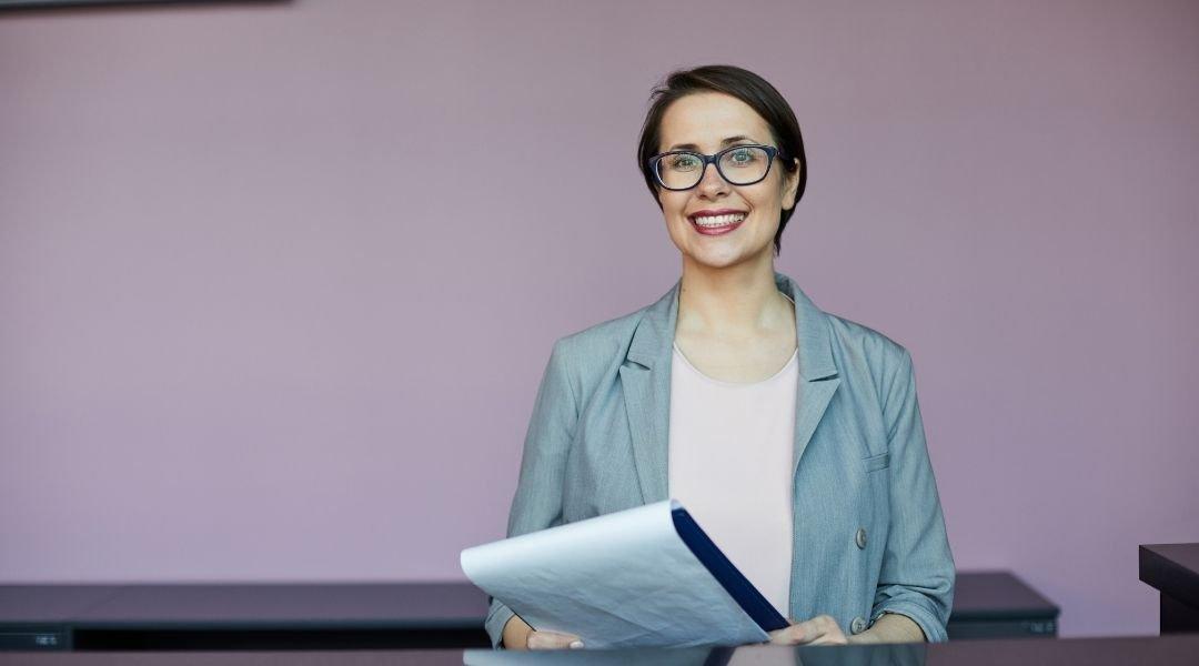 Mulher bonita e confiante feliz usando óculos, parada no balcão e segurando a prancheta enquanto preenche documentos. Visto Australiano