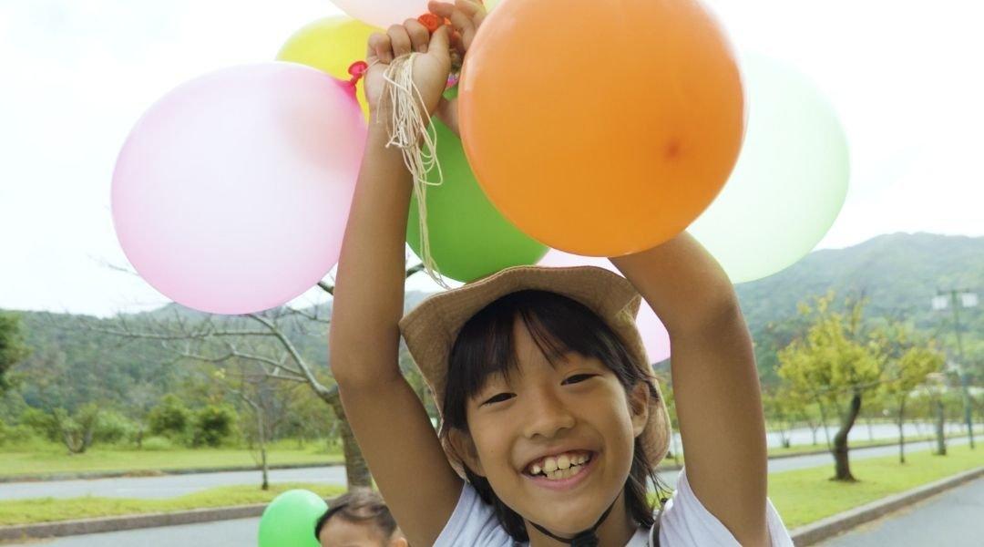 criança japonesa com um balãõ em um parque. Visto japonês.