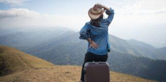 Viagem Internacional Sozinho: Mulher sentada em cima de uma mala de viagem sozinha em uma colina